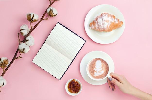 Mani in possesso di caffè e notebook con cornetto e ramo di cotone