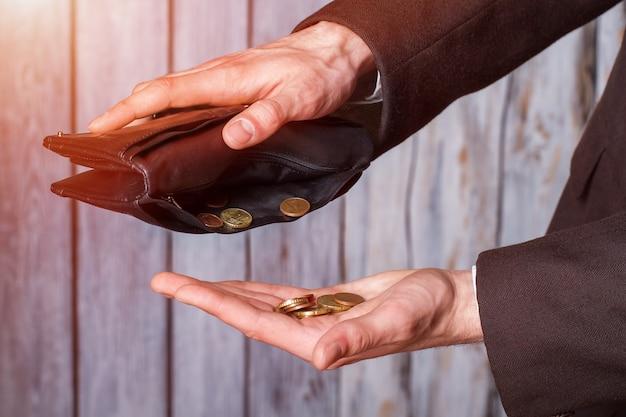 Mani che tengono monete e portafoglio. portafoglio nero e piccole monete. non un centesimo in più. la definizione di povertà.