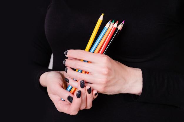Mani che tengono le matite colorate