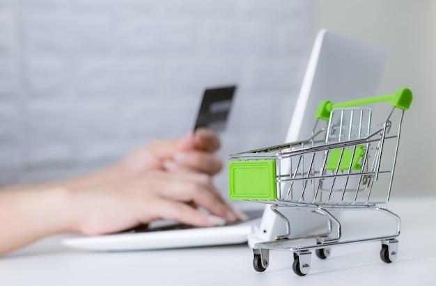 Mani che tengono la carta di credito sulla tastiera shopping online sul computer portatile