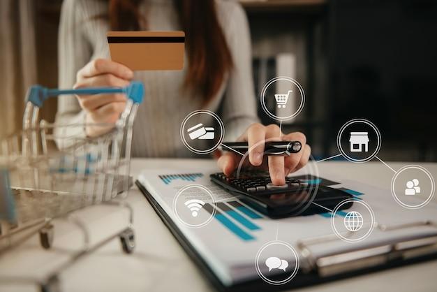 Mani che tengono la carta di credito e utilizzano la calcolatrice. acquisti online.