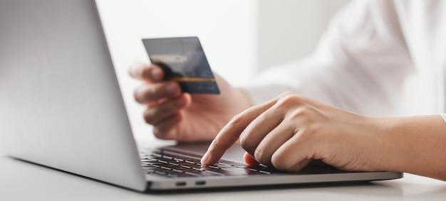 Mani in possesso di carta di credito e utilizzo di computer portatile, imprenditrice che lavora a casa, shopping online, e-commerce, spesa di denaro, internet banking.