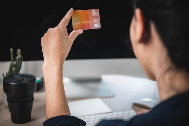Mani che tengono la carta di credito e che per mezzo del computer portatile. acquisti online
