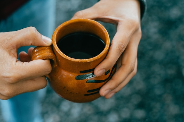 Mani che tengono una tazza di cafã© de olla, tradizionale dal messico.