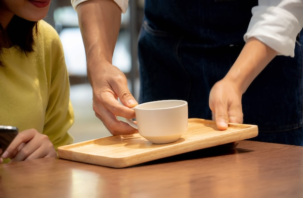Mani che tengono una tazza di caffè per il cliente nella caffetteria.