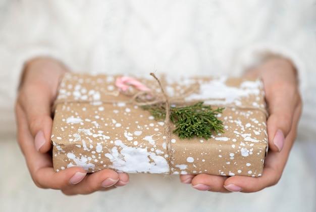 Mani che tengono il regalo di natale decorato