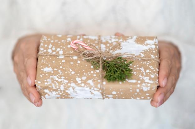 Mani che tengono regalo di natale decorato