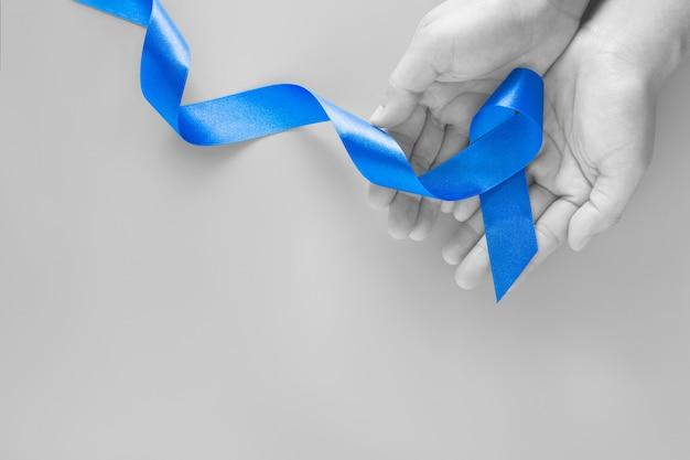 Mani che tengono il nastro blu profondo su sfondo blu con spazio di copia. consapevolezza del cancro del colon-retto cancro al colon delle persone anziane e giornata mondiale del diabete prevenzione degli abusi sui minori. sanità, concetto di assicurazione