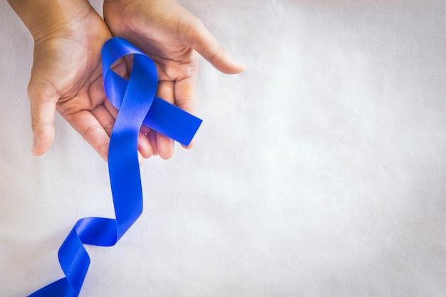 Mani che tengono il nastro blu profondo su tessuto bianco con lo spazio della copia consapevolezza del cancro del colon-retto cancro al colon della persona anziana e giornata mondiale del diabete prevenzione degli abusi sui minori