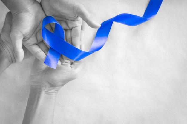 Mani che tengono il nastro blu profondo su tessuto bianco con spazio di copia. consapevolezza del cancro colorettale, cancro al colon delle persone anziane e giornata mondiale del diabete, prevenzione degli abusi sui bambini. sanità, concetto di assicurazione.