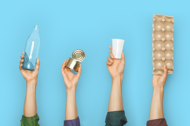 Mani che tengono diversi tipi di rifiuti