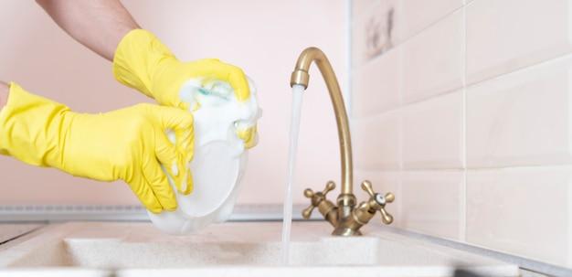 Una mano che tiene il piatto sporco e lo lava nel lavello della cucina versando acqua