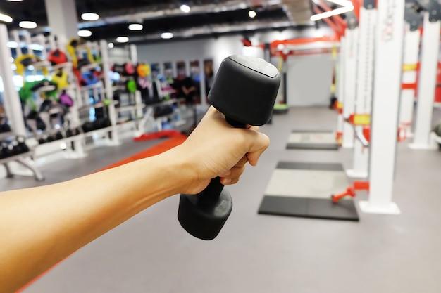 Mani che tengono manubri in palestra o palestra e sala fitness.