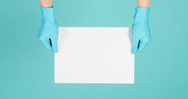 Le mani che tengono le maschere indossano guanti in lattice medico blu su sfondo verde menta o tiffany blue.