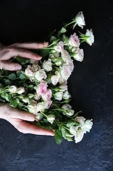 Mani che tengono i fiori su sfondo nero. mazzo di rose. perfetto piatto disteso con petali. cartolina per le vacanze madri felici. saluto per la giornata internazionale della donna. idea di compleanno per pubblicità o promozione.