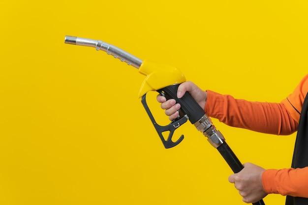 Mani che tengono l'ugello del carburante isolato sulla parete gialla