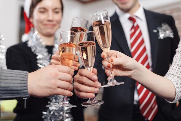 Mani che tengono i bicchieri di champagne facendo un brindisi in largo