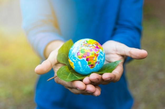 Mani che tengono globo e foglia
