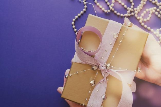 Mani che tengono il contenitore di regalo dorato con il fondo festivo del nuovo anno di natale di feste del nastro di scintillio rosa