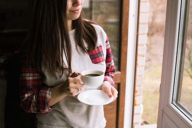 Mani che tengono tazza di caffè caldo al mattino