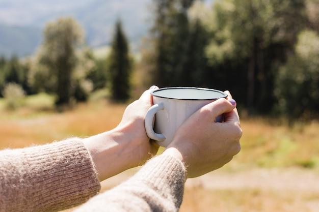 Mani che tengono tazza calda