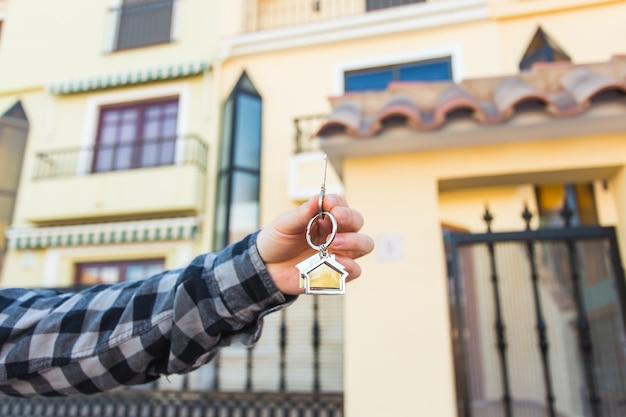 Mani che tengono le chiavi di casa sul portachiavi a forma di casa davanti a una nuova casa.