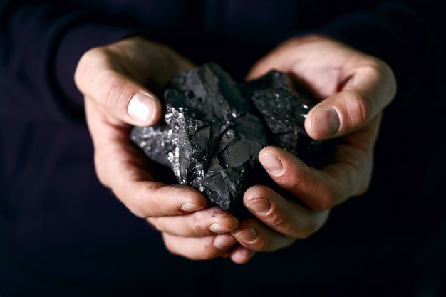 Mani che tengono pezzi di carbone