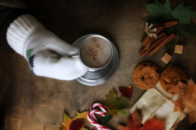 Mani che tengono una tazza di caffè caldo su un tavolo con foglie d'autunno