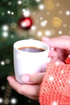 Mani che tengono tazza di bevanda calda, primo piano, sullo sfondo dell'albero di natale