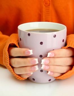 Mani che tengono la tazza di bevanda calda, primo piano