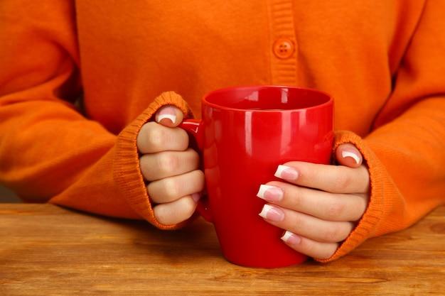Mani che tengono tazza di bevanda calda, primo piano