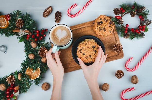Mani che tengono caffè e biscotto d'avena
