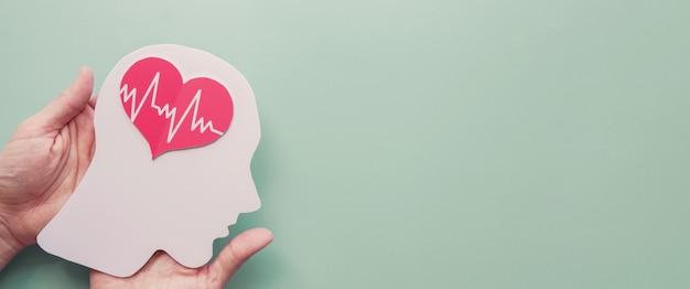 Mani che tengono cervello di carta e cuore, ictus cerebrale, concetto di giornata mondiale della salute mentale