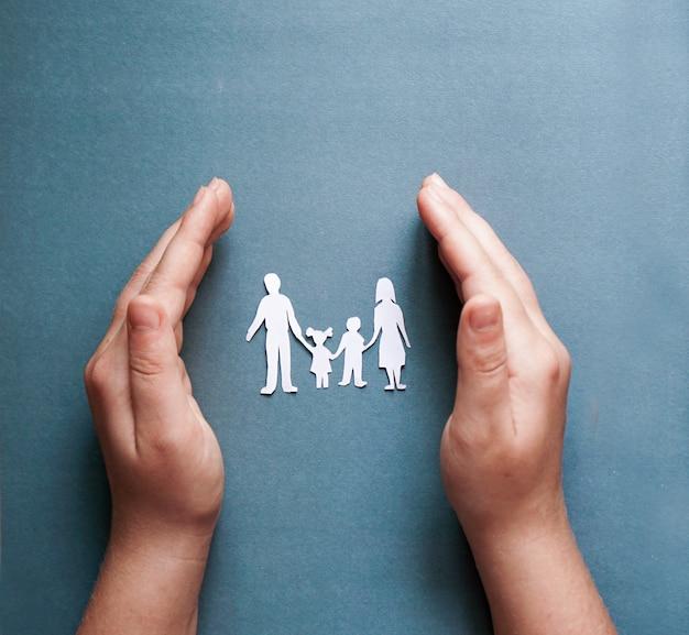 Mani che tengono il ritaglio di carta della famiglia, concetto di allontanamento sociale, covid19 sui precedenti blu di colore, protezione della famiglia