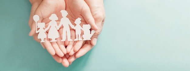 Mani che tengono il ritaglio di famiglia di carta, la giornata mondiale della salute mentale, il supporto per l'autismo, l'educazione a domicilio, il concetto di blocco
