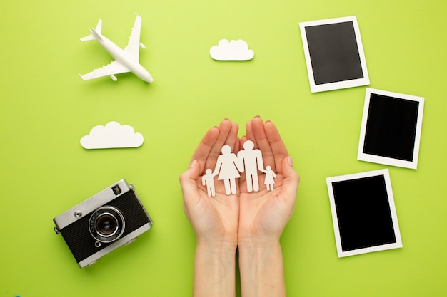 Mani che tengono la famiglia di carta accanto a foto istantanee