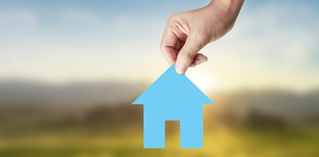 Mani che tengono casa di carta, casa di famiglia e protezione del concetto di assicurazione