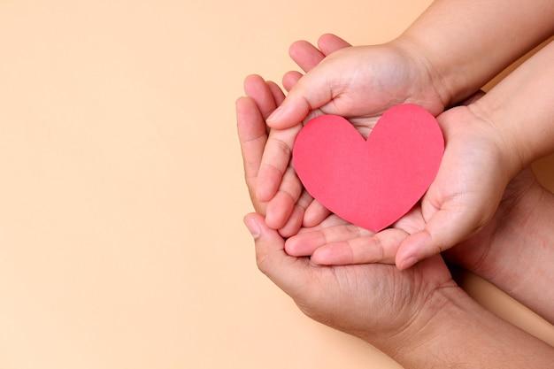 Mani che tengono il cuore di carta rosso, concetto di salute in famiglia.