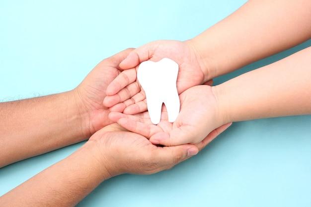 Mani che tengono i denti di carta sul blu