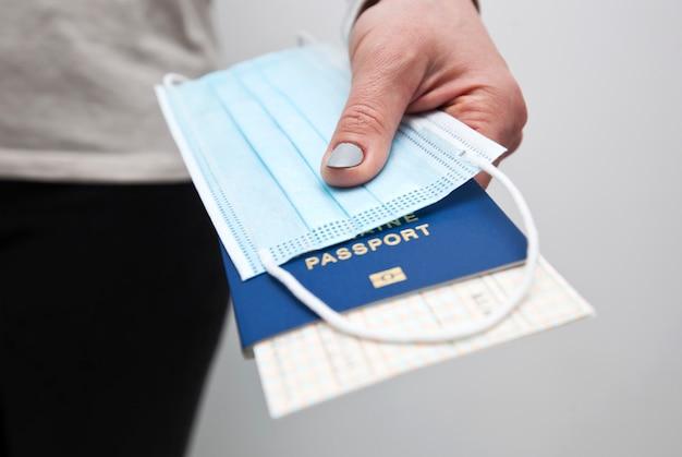 Mani che tengono un passaporto con il biglietto del treno e la mascherina medica