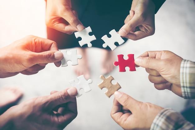Mani che tengono pezzo di puzzle in bianco per il successo di lavoro di squadra e il concetto di strategia.