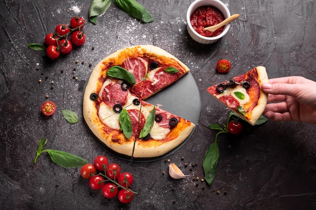 Mani che tengono un piese di pizza appena sfornata