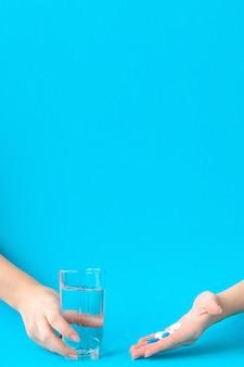 Mani che tengono le pillole e l'acqua su una parete blu