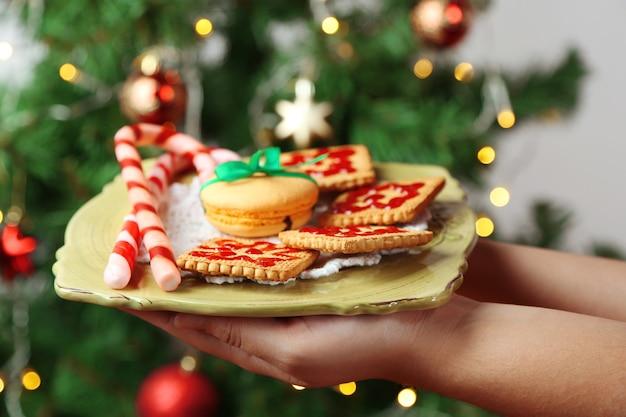 Mani che tengono piatto con biscotti e caramelle fatti in casa, su sfondo luminoso