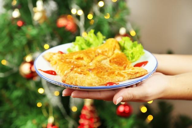 Mani che tengono piatto con hachapuri fatto in casa, su sfondo luminoso