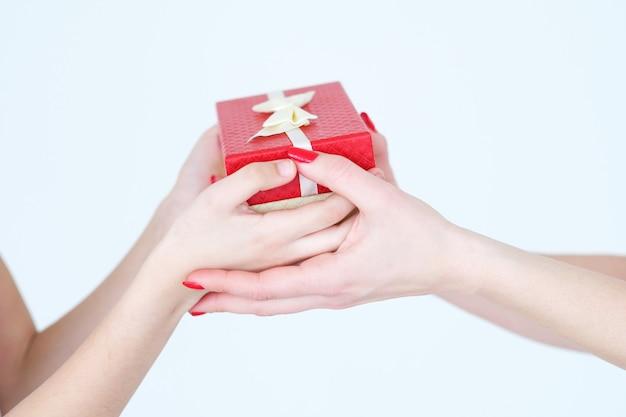 Mani che tengono presente in una confezione regalo rossa con un fiocco.