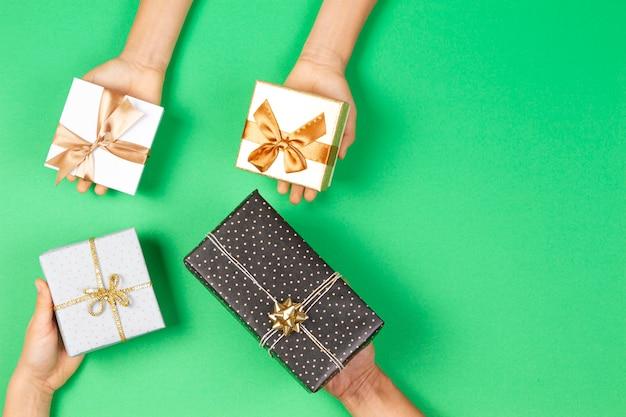 Mani che tengono le scatole dei regali su sfondo verde chiaro. vista dall'alto