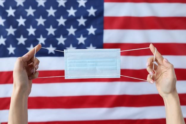 Mani che tengono la mascherina medica protettiva davanti alla bandiera degli stati uniti. nuovo concetto di ceppo di coronavirus