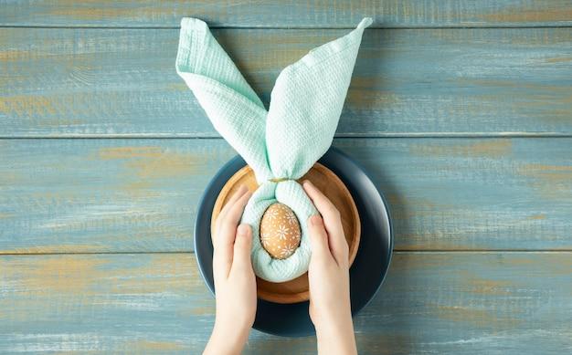 Mani che tengono uovo crudo con tovagliolo a forma di orecchie da coniglio