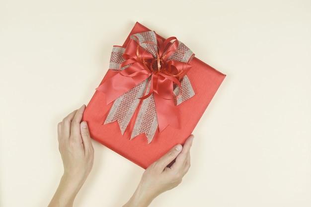 Mani che tengono una scatola regalo rossa presente per il compleanno il giorno di san valentino natale capodanno concept